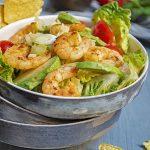 Grüner Salat mit Tomaten, Frühlingszwiebeln, Avocado und Curry-Garnelen