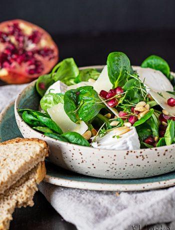 Knackig frischer Feldsalat mit Ziegenkäse und Parmesan; dazu ein Dressing mit Himbeeressig und Granatapfelkernen.