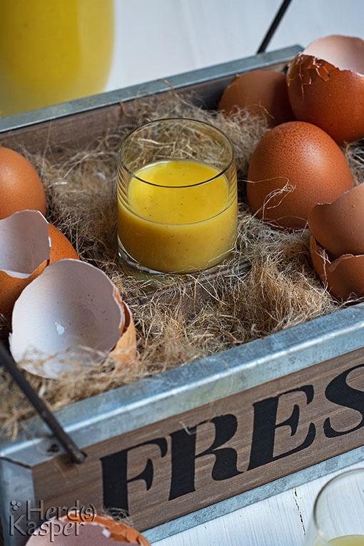 Ein Korb mit Stroh; darin die Schalen aufgeschlagener Eier und ein Gläschen Eierlikör.