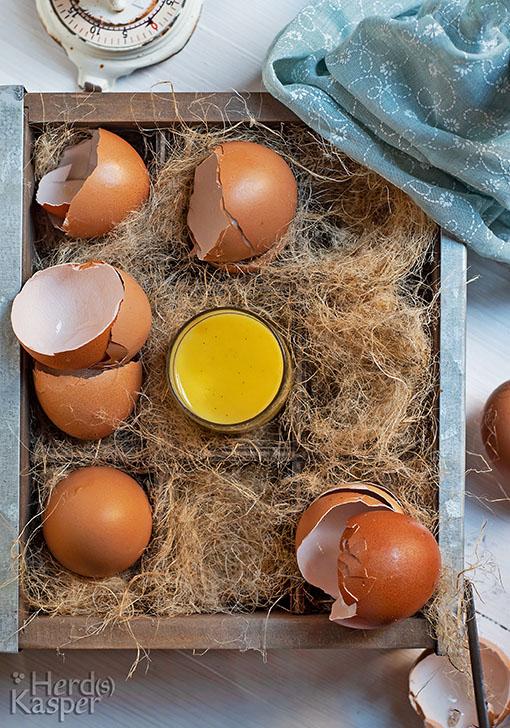 Ein Korb mit Stroh, darin die Schalen aufgeschlagener Eier und ein Gläschen Eierlikör.