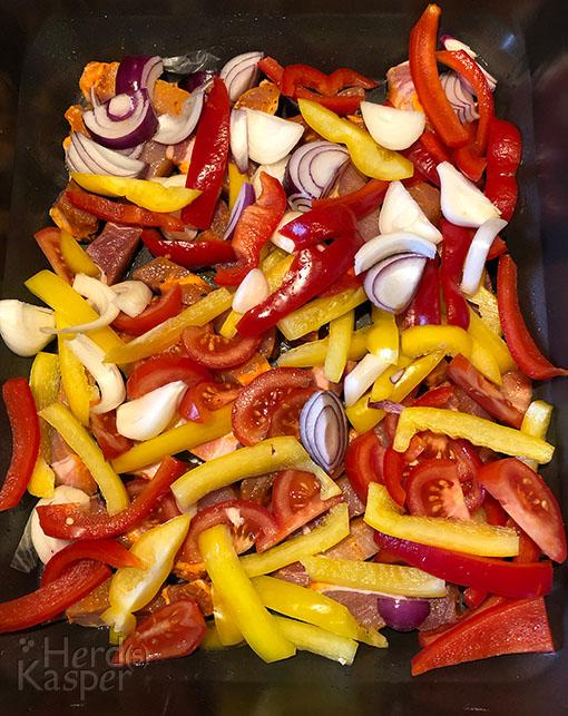 Streifen vom Nackensteak und frisches Gemüse werden in einer Back- oder eingeölten Auflaufform geschichtet.