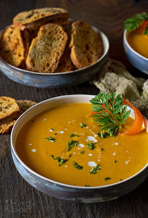 Karottensuppe mit Orangen; im Hintergrund Brot-Chips.